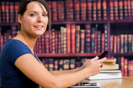 Woman smiling with phone in library of college photo