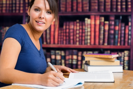 Smiling woman and writing in university library photo