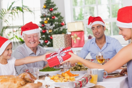 Mother giving daughter christmas present at christmas dinner photo
