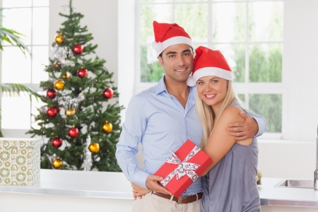 Happy couple holding a gift at christmas photo