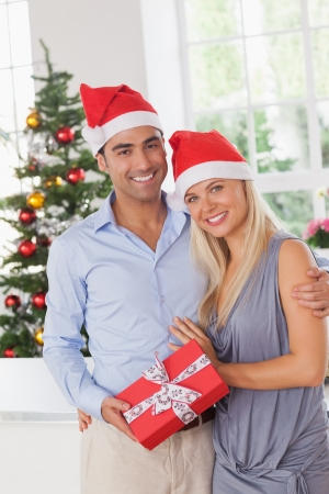 Attractive couple at christmas holding a gift photo