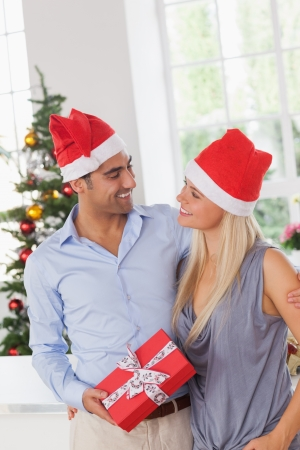 Smiling couple at christmas wearing santa hats photo