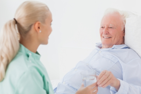 Home nurse giving elderly man in bed a glass of water photo