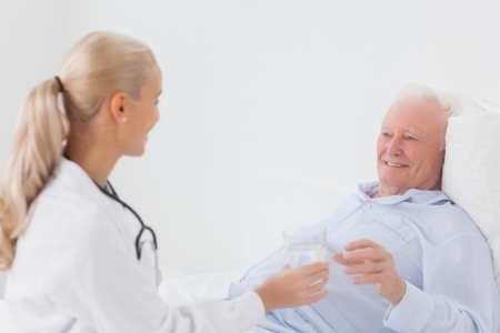 doctor giving glass: Doctor handing glass of water to elderly patient