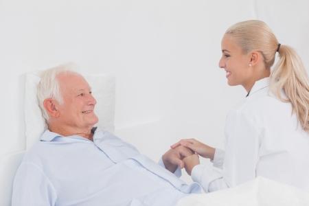 Doctor comforting elderly patient in bed photo