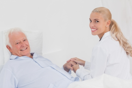 Smiling doctor holding hand of elderly patient in bed photo
