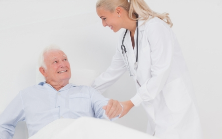 Doctor helping elderly man in bed to sit up photo