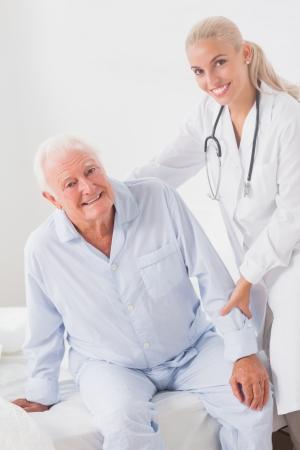 Smiling doctor helping elderly man to sit up photo
