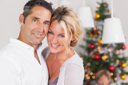 Couple embracing at christmas by dinner table photo