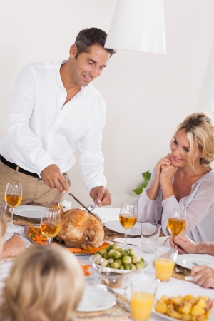 Father carving the turkey at the head of table at thanksgiving photo