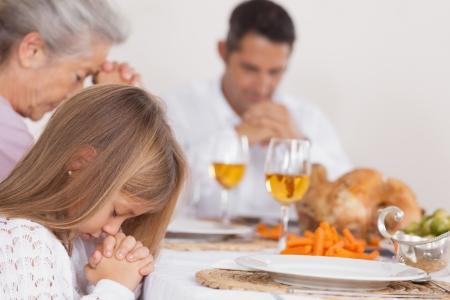 family praying: Niña dar gracias con la familia antes de la cena de Acción de Gracias Foto de archivo