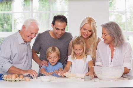 Children having fun baking with family watching them photo