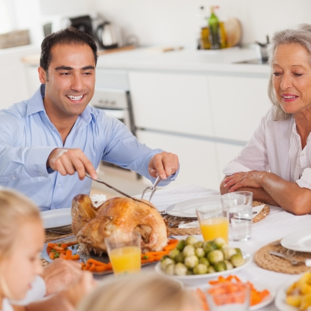 Man carving the thanksgiving turkey at head of table photo