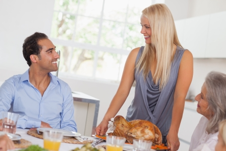 thanksgiving adult: Happy wife bringing turkey to the table at thanksgiving Stock Photo