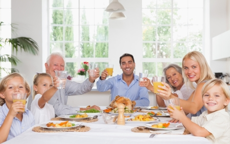 Happy family toasting around the table at thanksgiving dinner photo