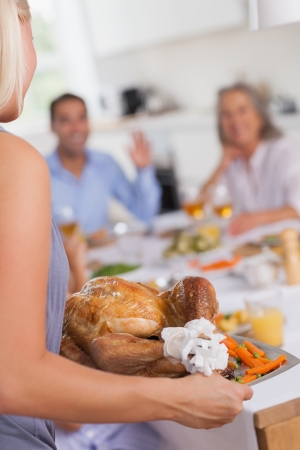 bringing: Blonde woman bringing thanksgiving turkey to the dinner table