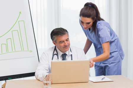 Smiling doctor showing nurse something on laptop photo