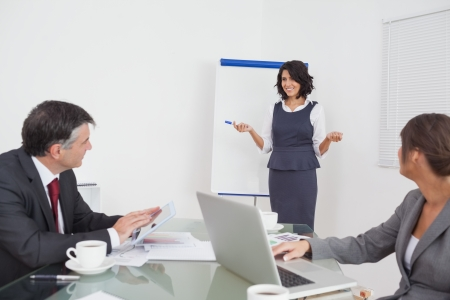 Businesswoman explaining to her colleagues using a tablet and a computer in office Stock Photo - 18121583