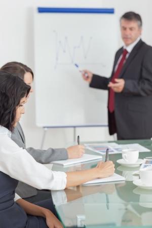 dictating: Dictando Empresario y sus colegas tomando notas estrechamente Foto de archivo