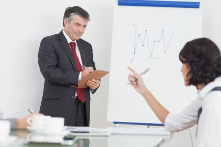 Businessman writing on his clipboard and smiling at his colleagues in office Stock Photo - 18119238