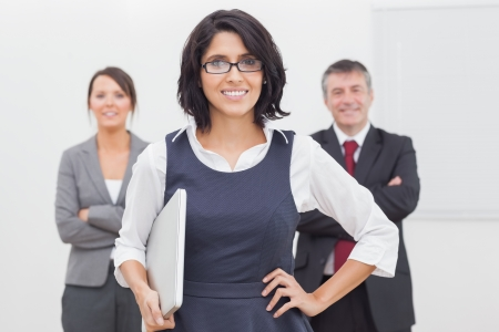 Smiling businesswoman and her team and laptop Stock Photo - 18119341