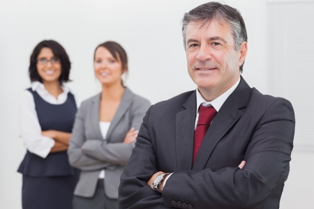 Businessman and his team smiling arms crossed in office Stock Photo - 18119338