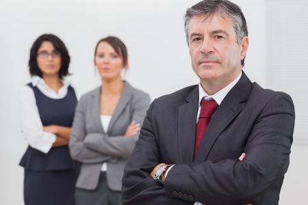 Businessman and his team standing with crossed arms in office photo