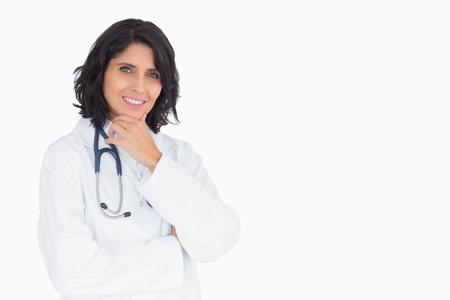 Smiling doctor with hand on chin on white background photo
