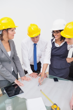 Team looking at a construction plan and laughing in office Stock Photo - 18119794