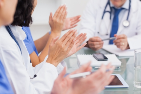 Nurses clapping a doctor during meeting photo