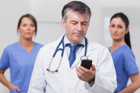 Doctor looking at phone with his team of nurses in the background photo