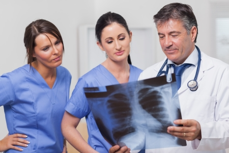 Doctor and nurses looking at x-ray seriously photo