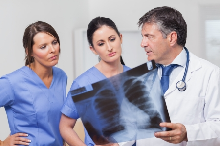 Doctor speaking about x-ray with nurses seriously photo