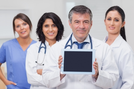 Doctor showing tablet pc with his team behind him photo