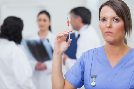 Nurse holding syringe with her team behind her photo