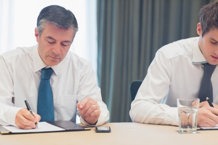 Businessmen taking notes at a meeting photo