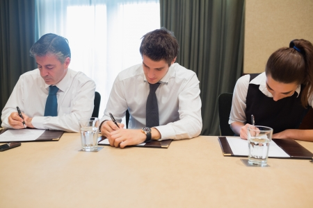 Business people taking notes at desk during meeting photo