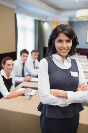 Businesswoman standing with arms crossed in conference photo