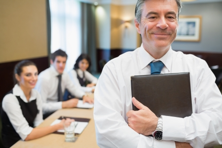 Businessman holding folder at conference standing and smiling photo