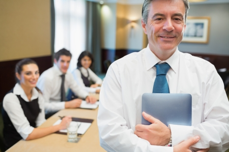 Businessman holding digital tablet at meeting standing and smiling photo