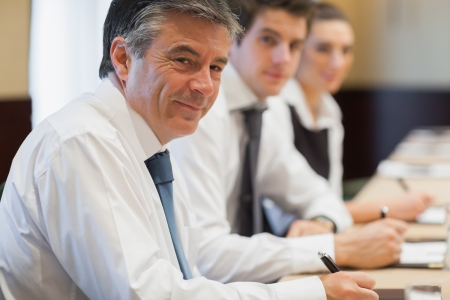 taking note: Sorridente uomo d'affari prendere appunti durante le riunioni