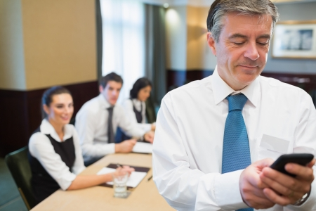 Businessman texting during meeting photo