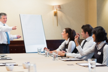 Woman asking question during business presentation in conference room photo