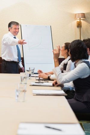 Smiling man pointing during presentation in conference room photo