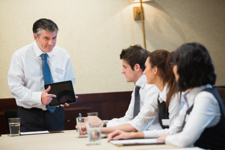 Businessman using tablet in meeting in conference room photo