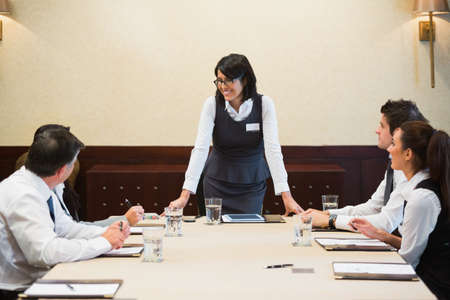 Happy businesswoman standing at head of table in conference room Stock Photo - 18120476