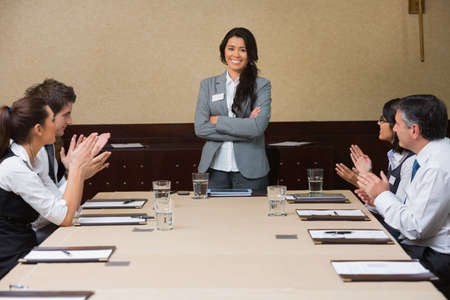 Businesswoman being applauded by peers in conference room photo