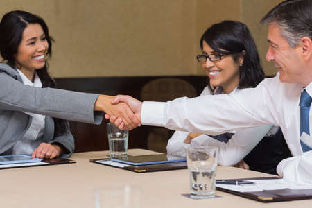 agreement: Business people shaking hands during meeting