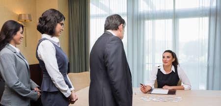 welcome desk: Line of business people at registration desk in conference room