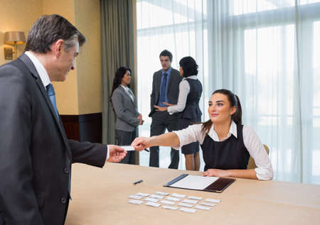 registration: Woman handing name tag to businessman at welcome desk at conference